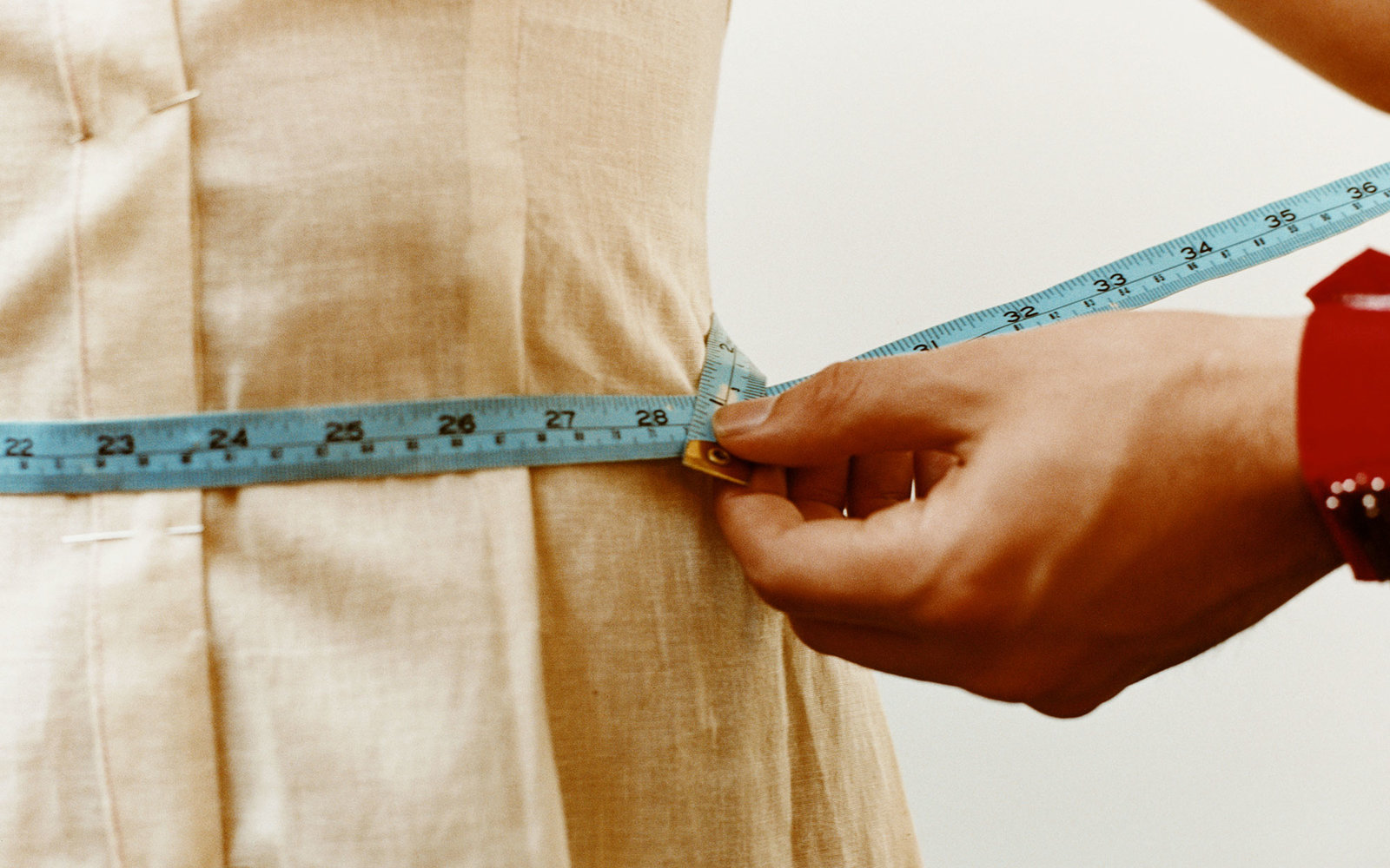 Tailor measuring woman's waistline, close-up