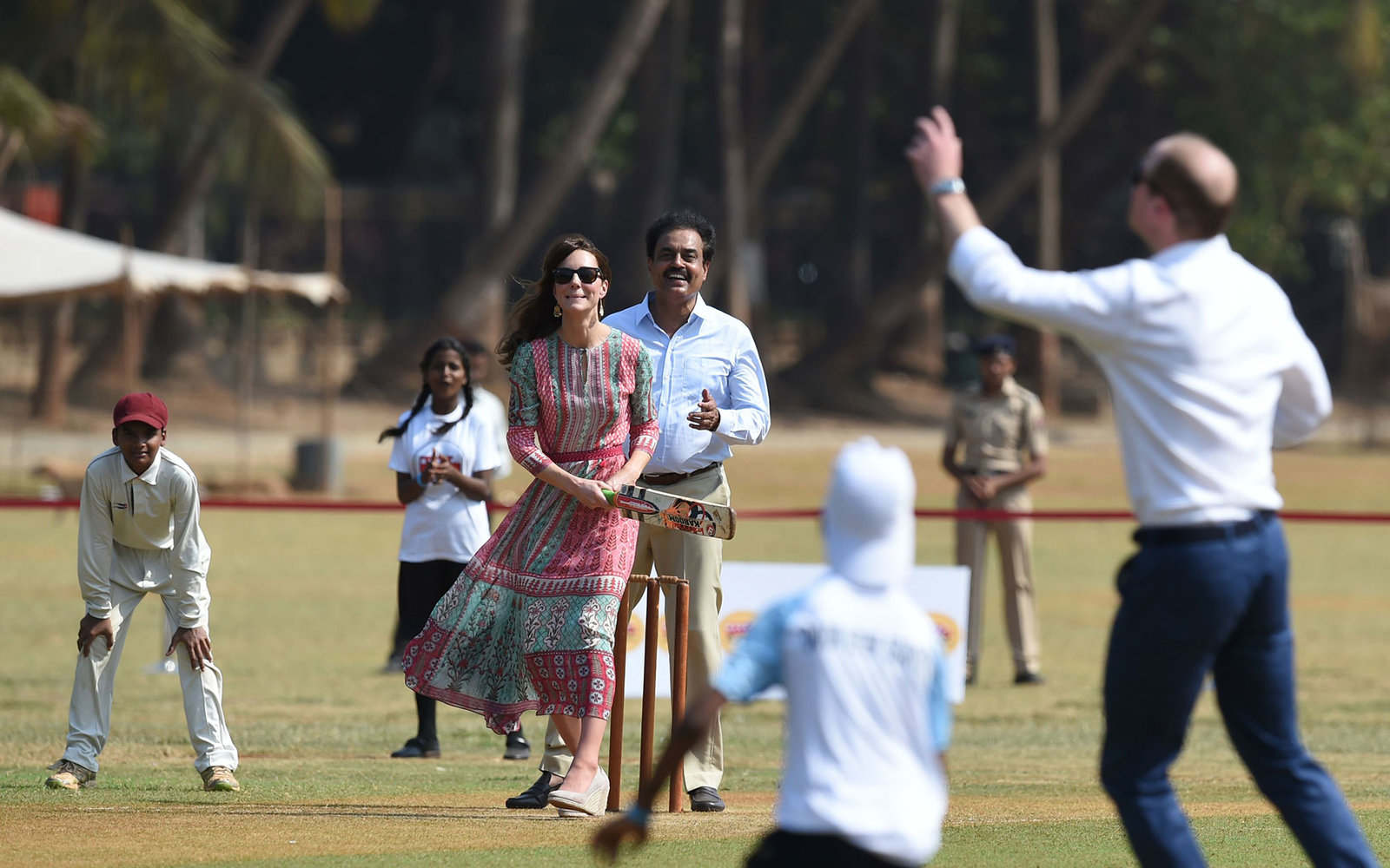 Catherine, Duchess of Cambridge(C) looks on as she and Prince William, Duke of Cambridge(R) play a game of cricket with Indian children who are beneficiaries of NGO's at The Oval Maidan in Mumbai on April 10, 2016. / AFP / INDRANIL MUKHERJEE        (Photo