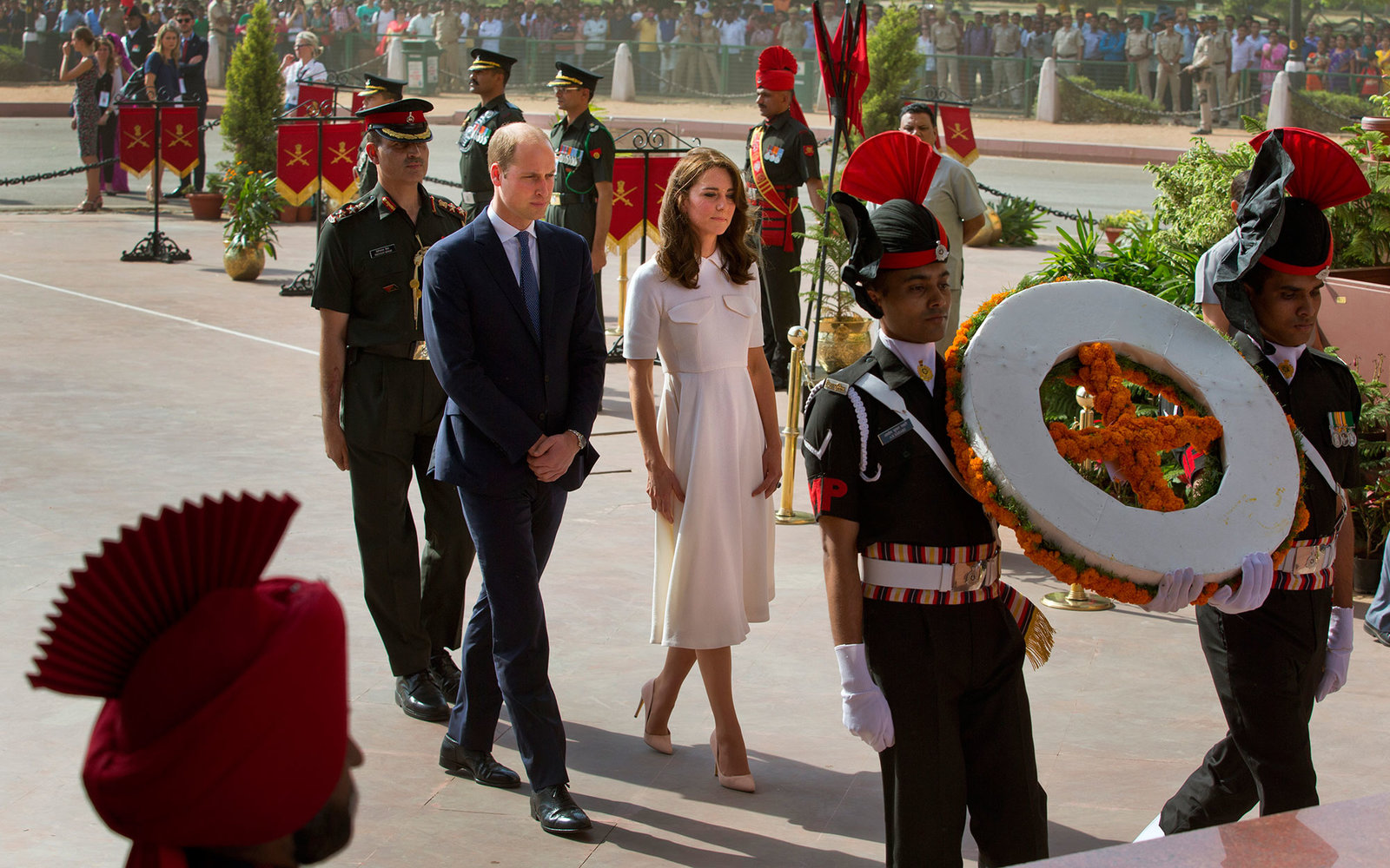 Britain's Prince William,Duke of Cambridge(C)along with his wife Catherine,Duchess of Cambridge(C/R)walk behind a wreath laying party as they their tributes at the India Gate war memorial, in the memory of the soldiers from Indian regiments who served in