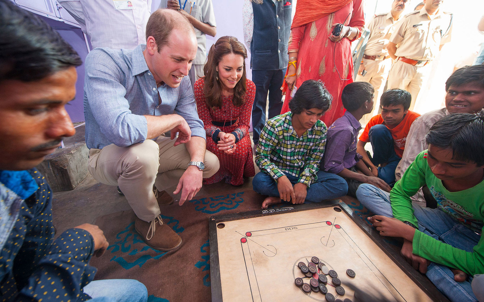 NEW DELHI, INDIA - APRIL 12:  Catherine, Duchess of Cambridge and Prince William, Duke of Cambridge play a game of carrom with street children at a contact centre run by the charity Salaam Baalak, which provides emergency help and long term support to hom