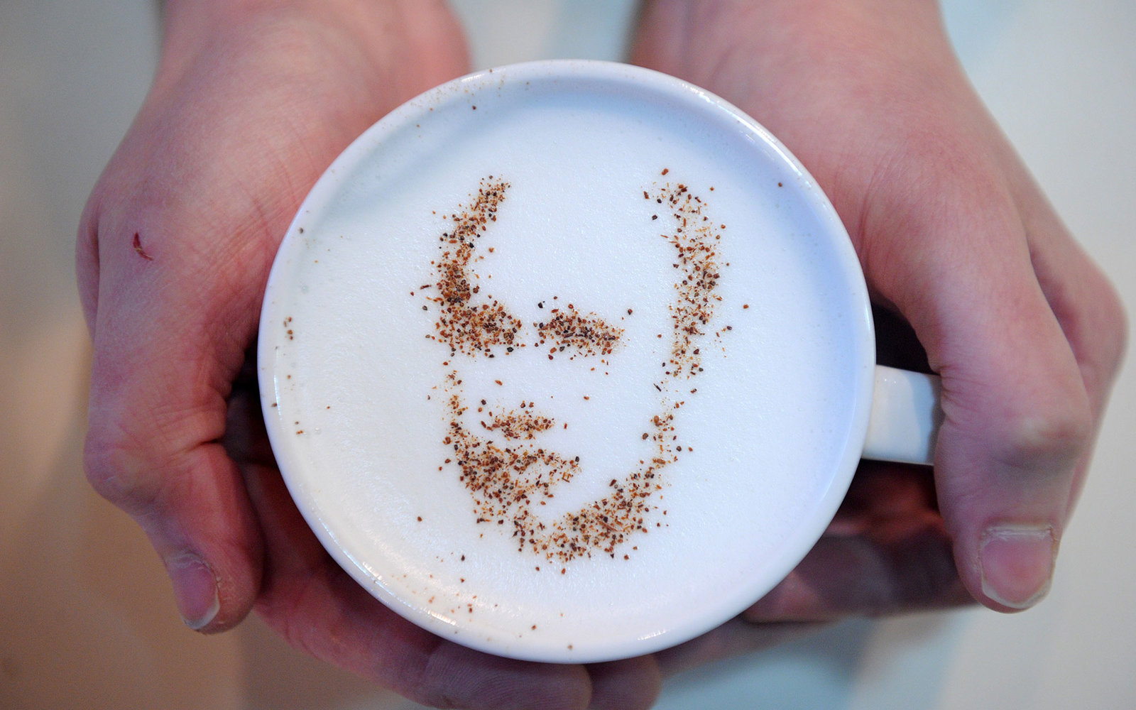 A coffeehouse client holds a cup of cappuccino with the portrait of Vladimir Putin created with cinnamon and cocoa powder sprinkled on the cappuccino's foam in Moscow, on February 1, 2012. The strongman prime minister is seeking to win back his old Kremli