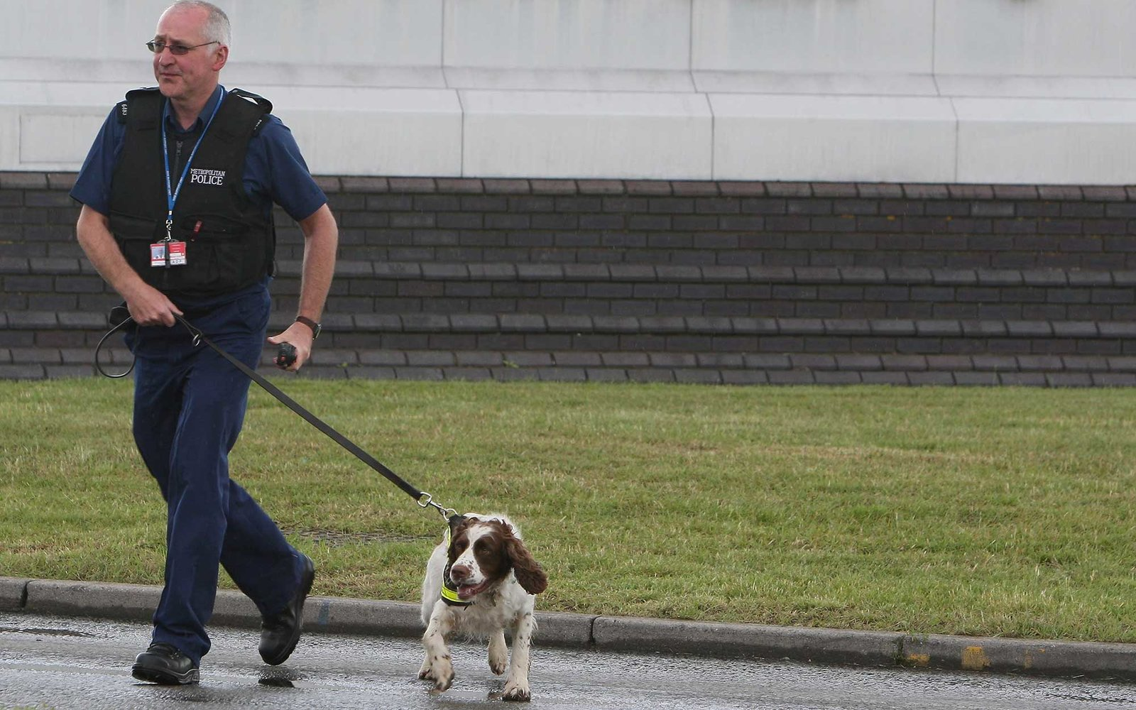 LONDON - JULY 03:  A police officer and sniffer dog head towards Terminal 4, Heathrow Airport as evacuated passengers depart on July 3, 2007 in London, England. Officials at Heathrow Terminal 4 have confirmed they have a suspect bag which has caused major