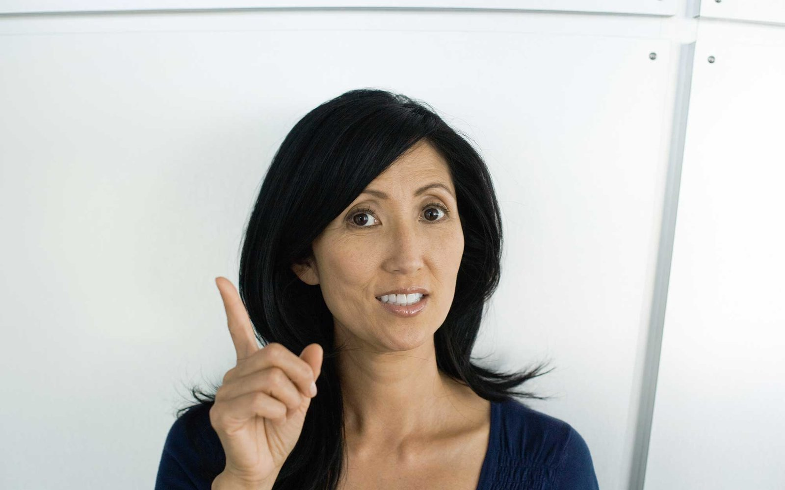 Woman holding up finger, looking at camera