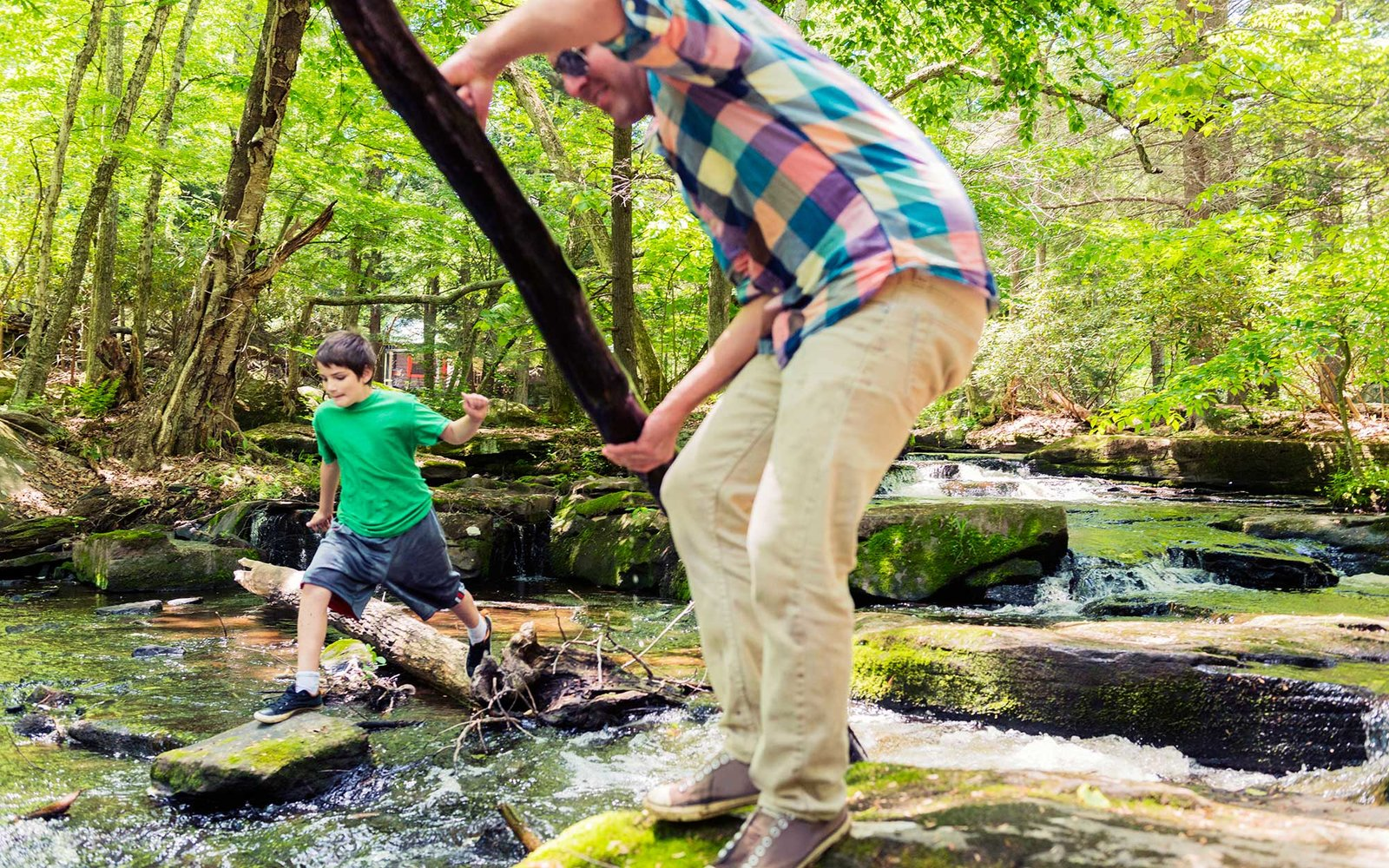 This is a horizontal, color, royalty free stock photograph of a young, caucasian, 10 year old American boy on summer vacation in the Catskill Mountains in upstate New York, United States. He jumps from rock to rock to cross the wooded stream in the forest