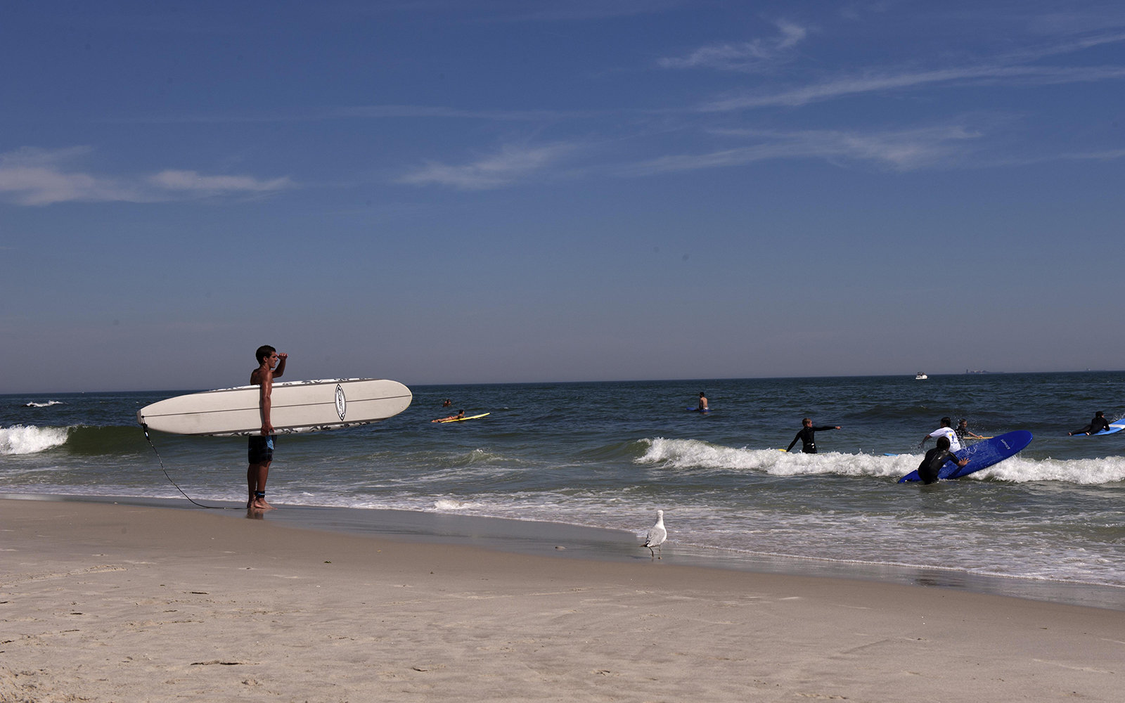 Man holding surfboard at Long Beach in New York, USA