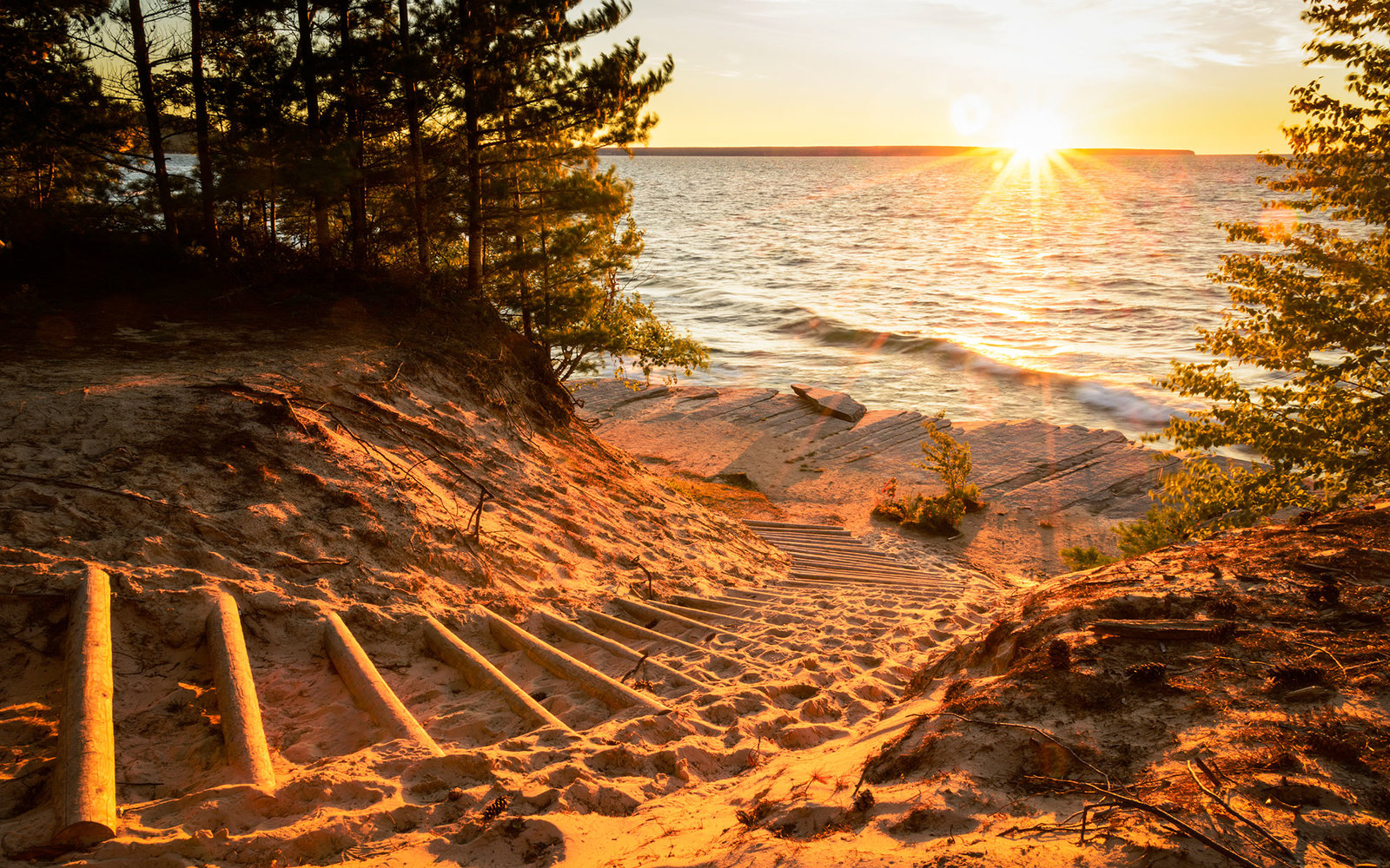 Stairway of logs going down to Lake Superior, into the bright sunshine.