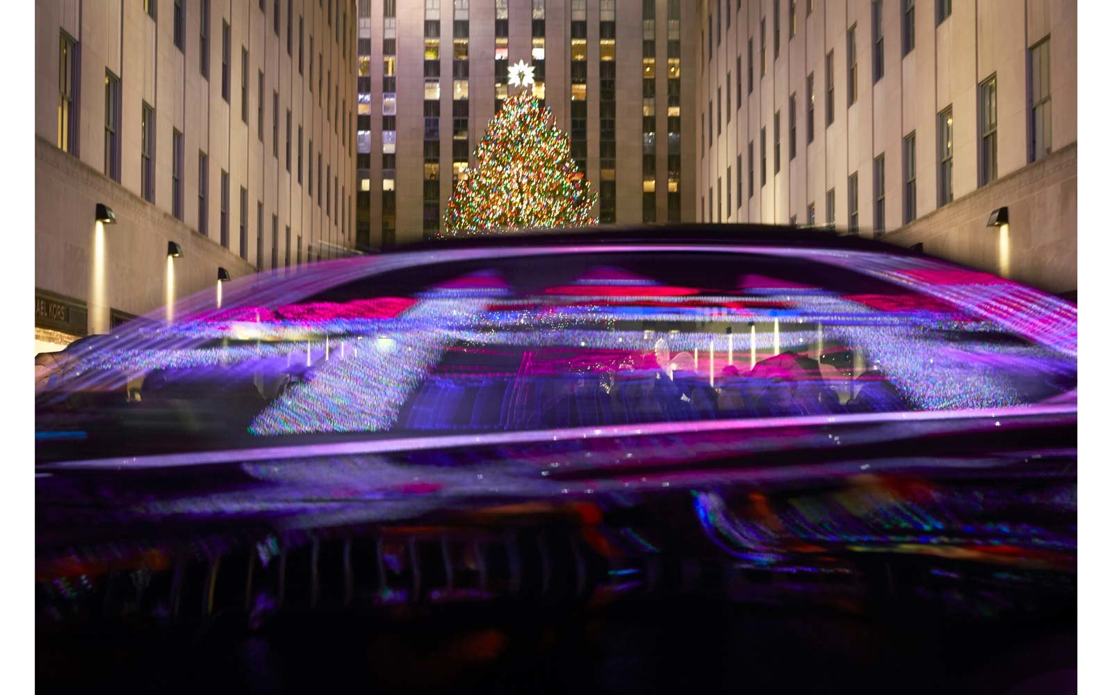 The tree at Rockefeller Center with the Saks windows in reflection