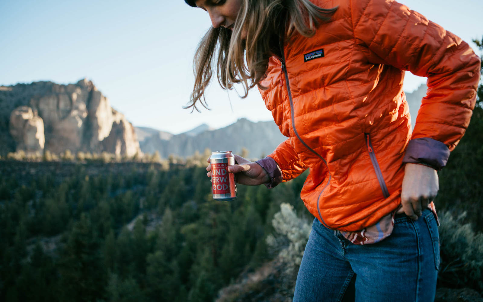 Woman climbs mountain holding wine in a can