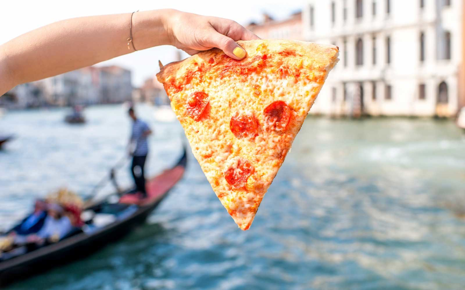 Young female traveler eating traditional italian pizza slice on the water canal background in Venice.