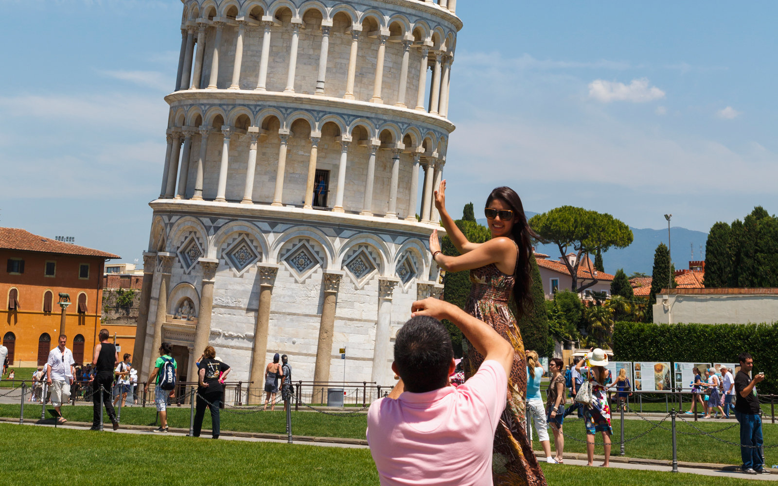 A woman poses as though she is holding up the Tower of Pisa.