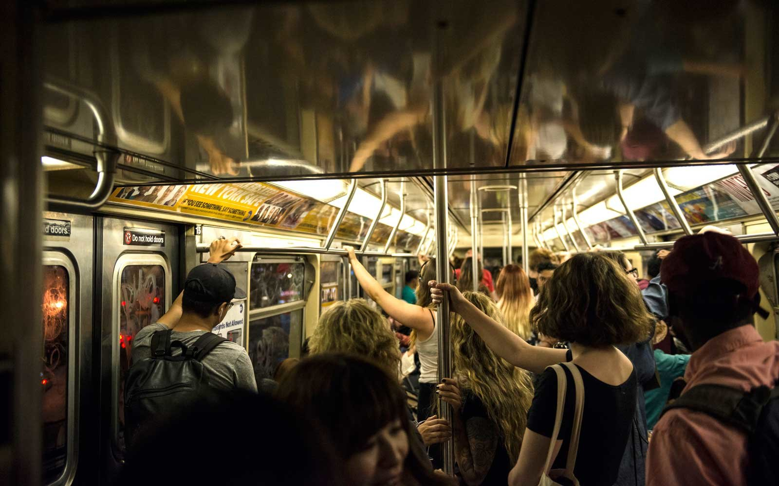 People ride a crowded subway train in New York City.