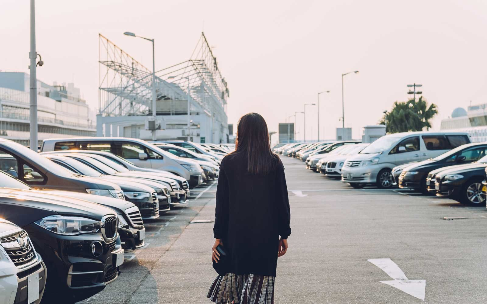 Rear view of young woman walking in an outdoor car park looking for her car.