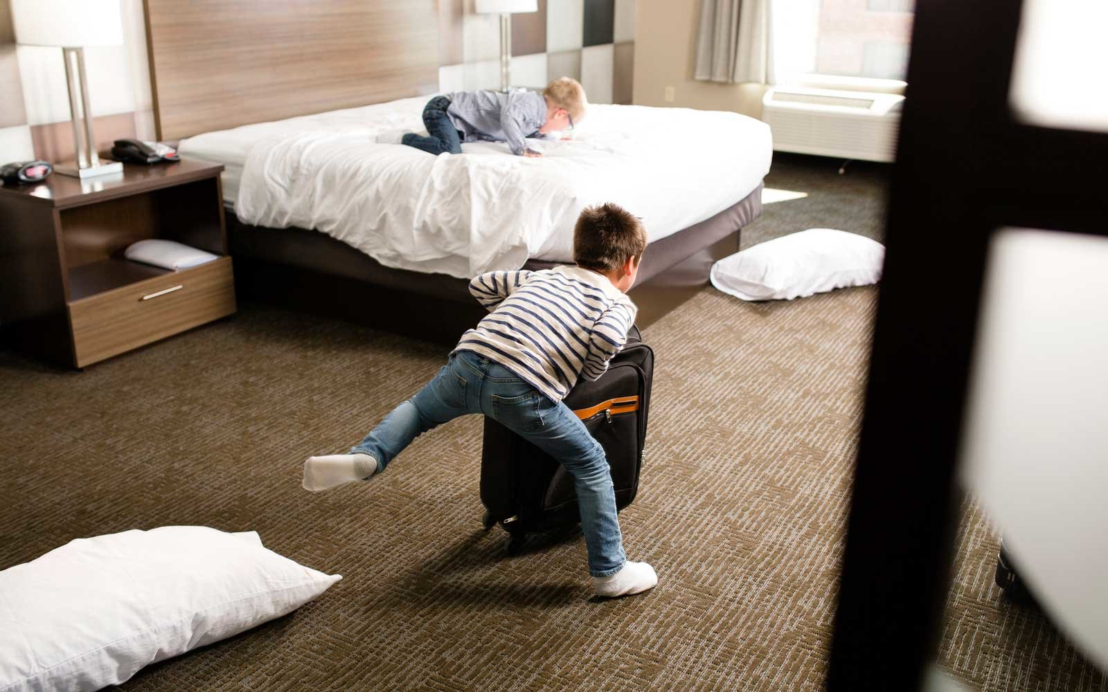 Two boys play in a hotel room.