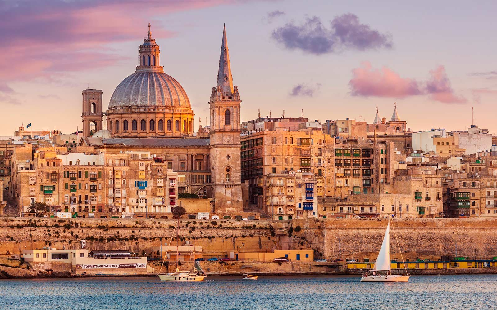 Valletta skyline at sunset with the Carmelite Church dome and St. Pauls Anglican Cathedral, Valletta, Malta, Mediterranean, Europe