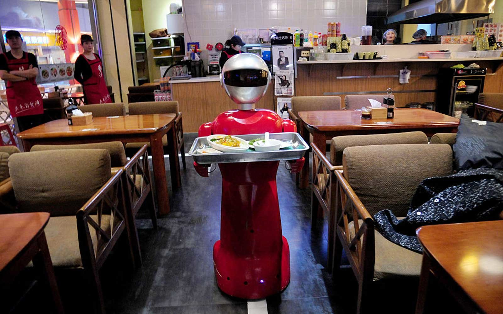 SHENYANG, CHINA - MARCH 15:  (CHINA OUT) A robot delivers meals for customers at a restaurant on March 15, 2016 in Shenyang, Liaoning Province of China. The robot which's in 140 centimeters high and 60 kilograms weight can communicate daily words with cus