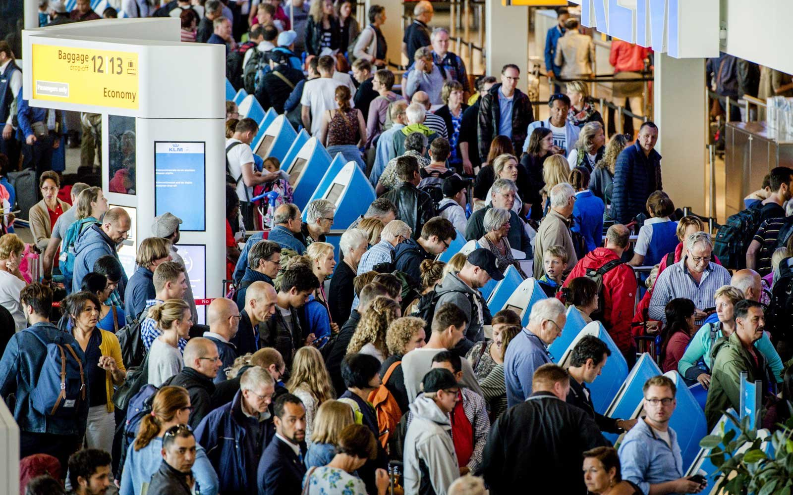 Travelers wait to check-in at Airport