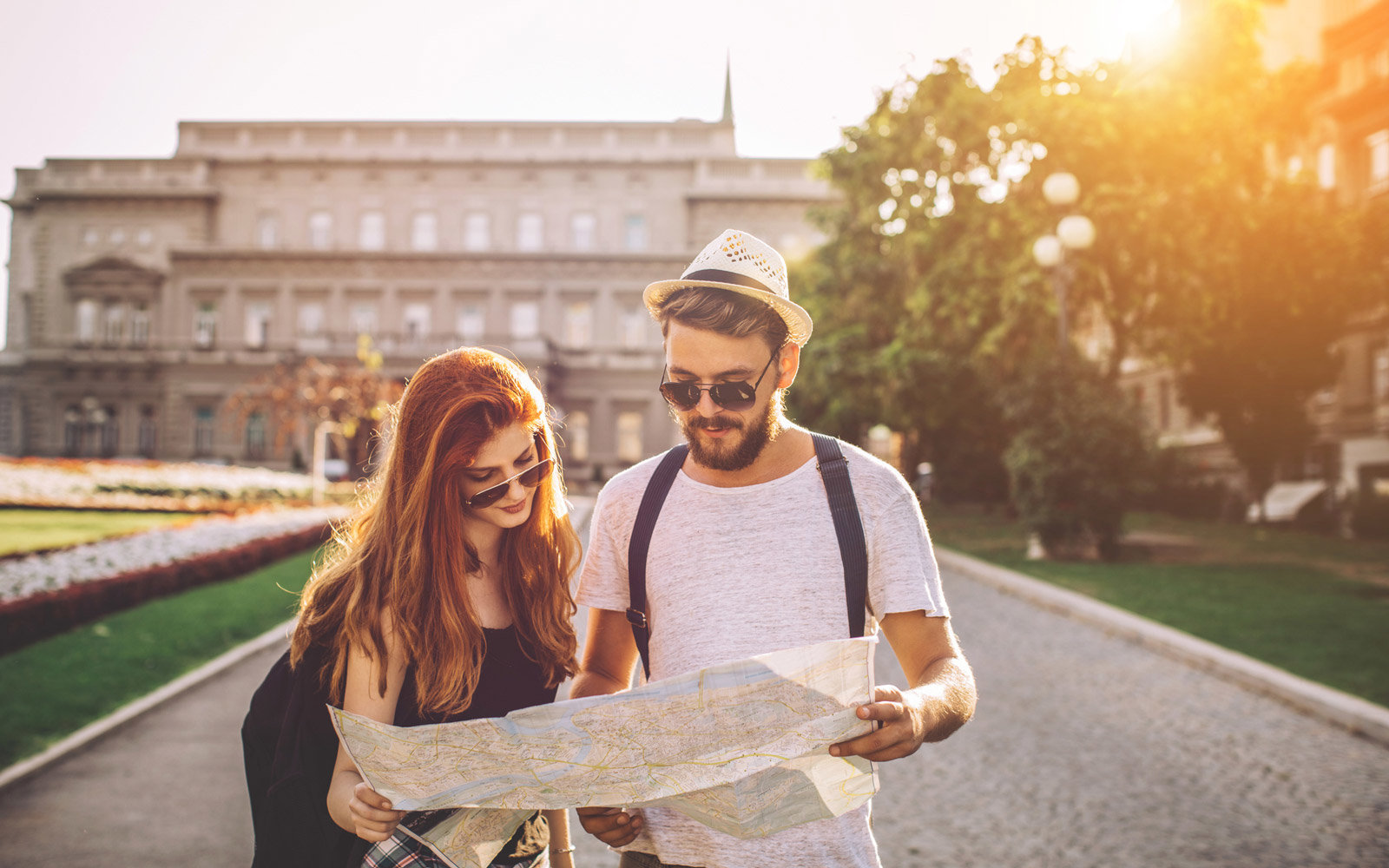 Young couple touring a foreign city. Holding map to find their destination. Wearing casual clothes. Enjoying in beautiful sunny day.