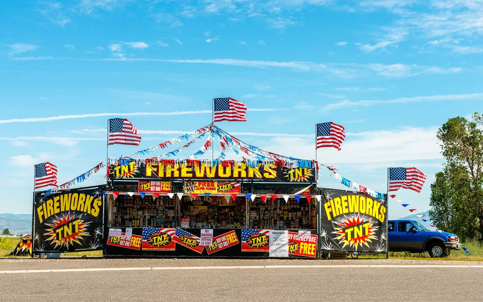 July 4th holiday, a fireworks stand is open for business on the side of the road. American flags decorate the stand which boldly advertises TNT and Fireworks