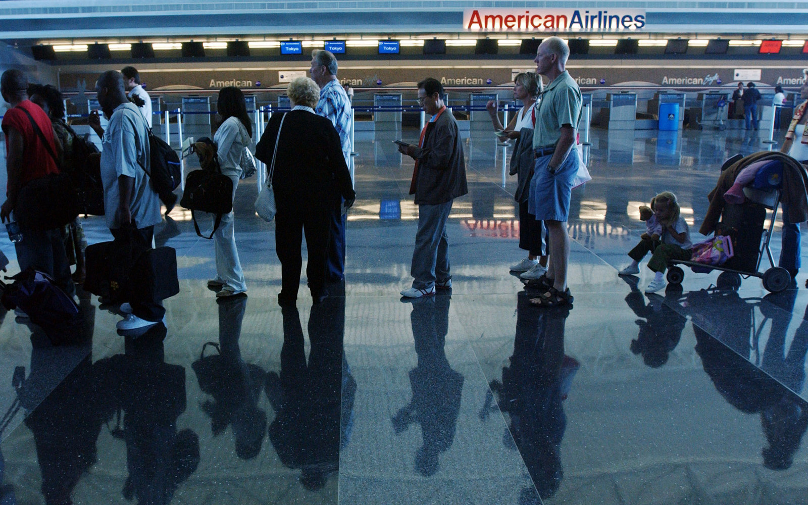 Passengers wait in line in front of an American Airlines ticket area.