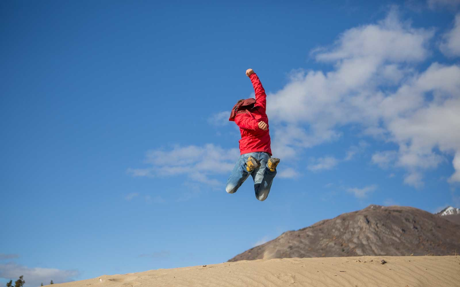 Young cheerful man in desert jumping high up in the air.