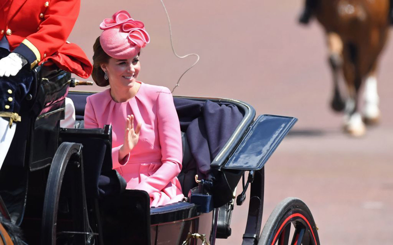 Britain's Catherine, Duchess of Cambridge waves as she travels in a horse-drawn carriage back to Buckingham Palace after attending 'Trooping the Colour' on Horse Guards Parade to mark the Queen's official birthday, in London on June 17, 2017.The ceremo