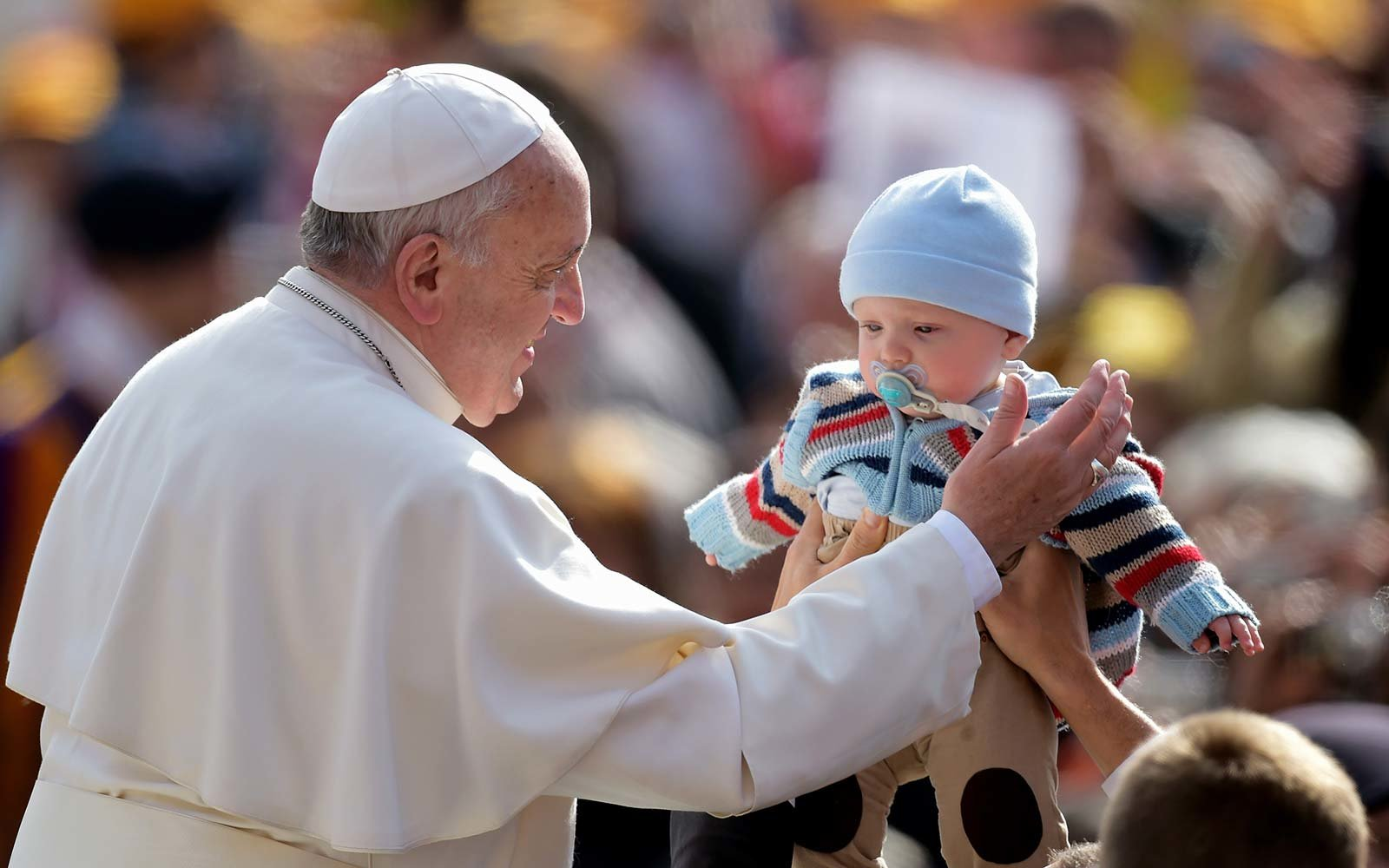 Pope Francis welcomes a baby upon his arrival at St. Peter's square at the Vatican Rome Italy