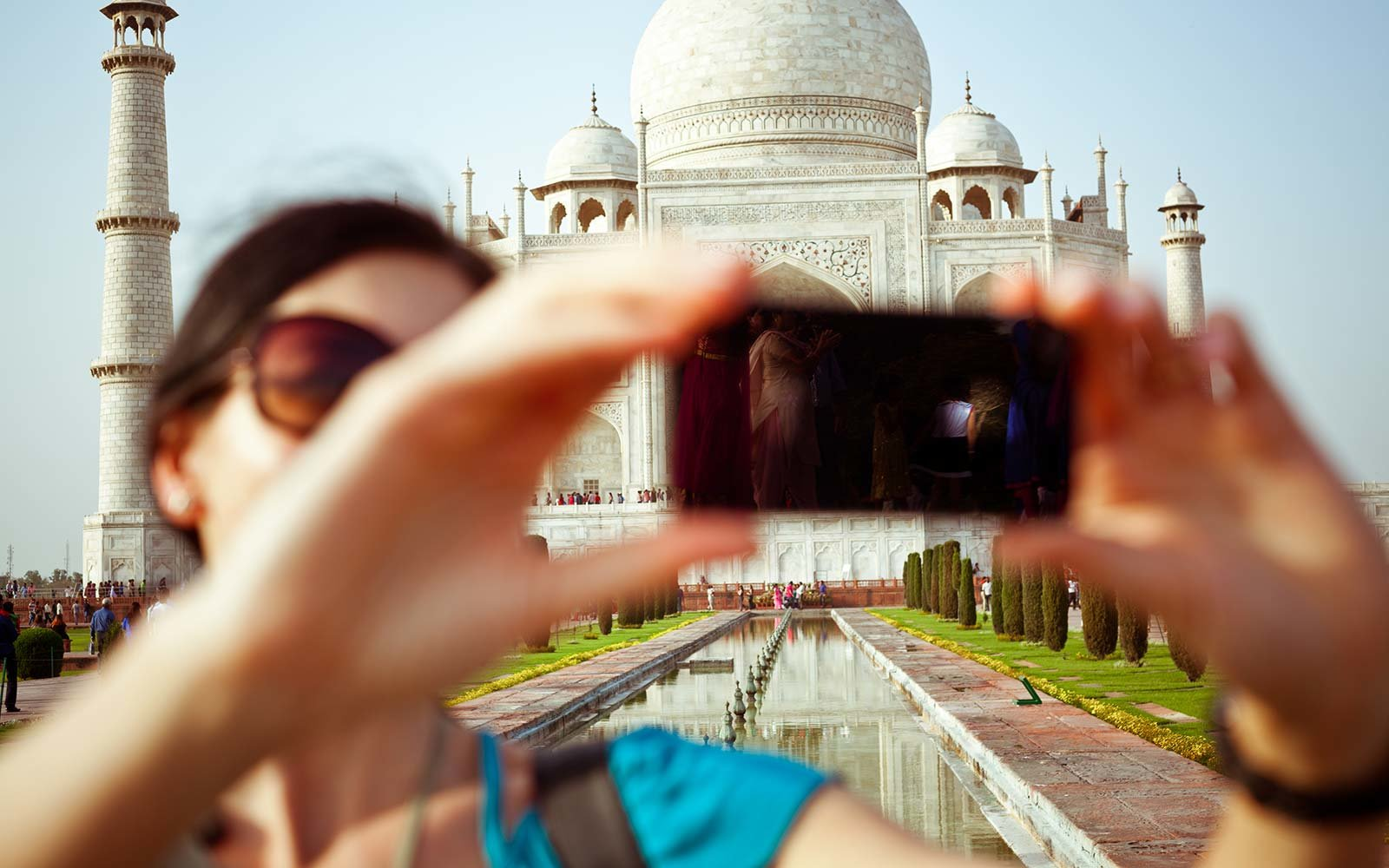 Female tourist taking selfie using smart phone with Taj Mahal in India