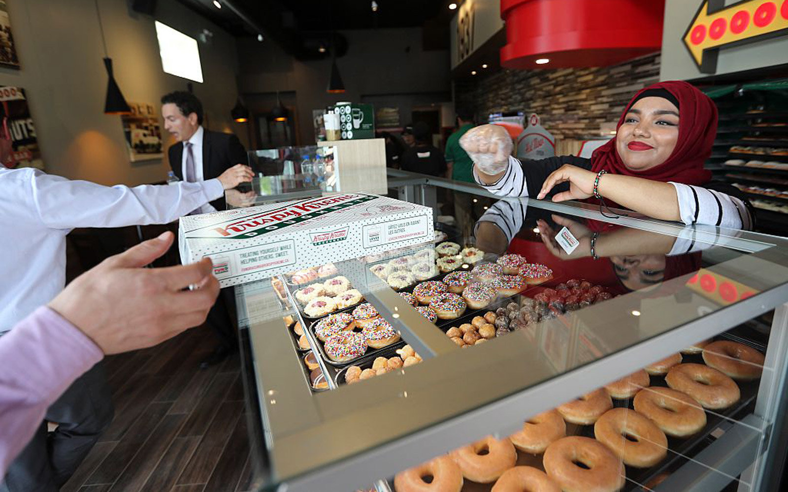 TORONTO, ON - MAY, 25   Retail Krew member Sadian Rahman passes over a box of assorted.After a not-so-sweet history in Toronto, Krispy Kreme opens new cafe concept in Toronto where you have the option of having your donuts served hot, and partners are ac