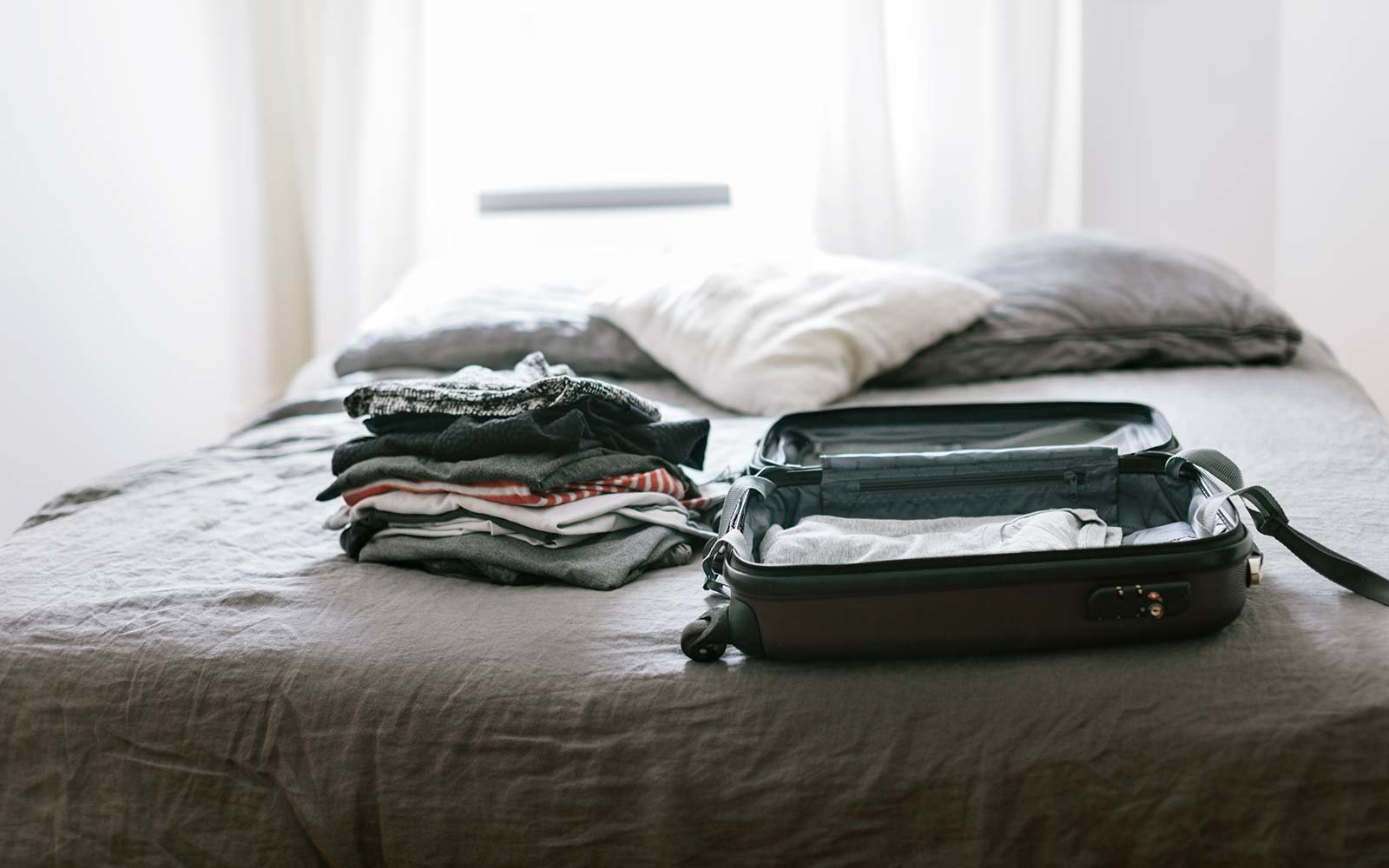 Open suitcase with clothing on Bed packing