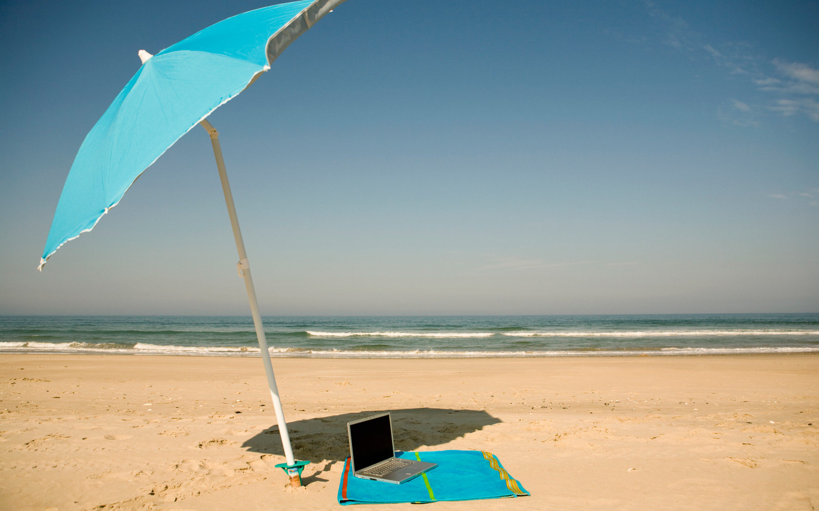 A laptop on the beach.