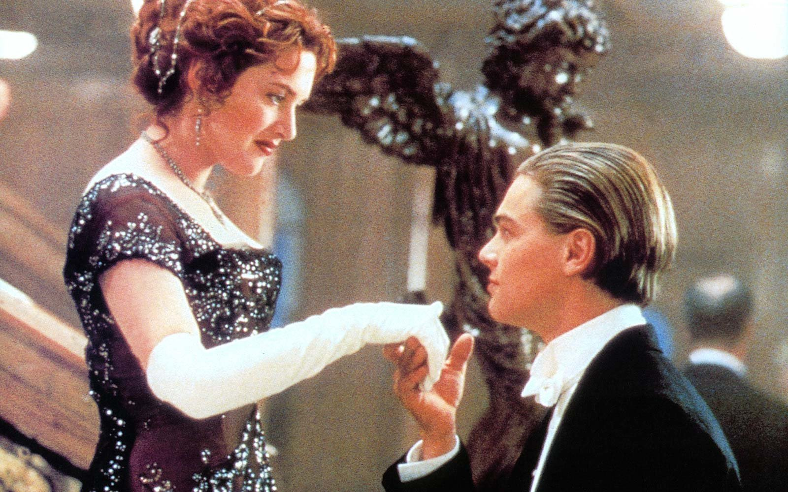 Kate Winslet offers her hand to Leonardo DiCaprio in a scene from the film 'Titanic', 1997