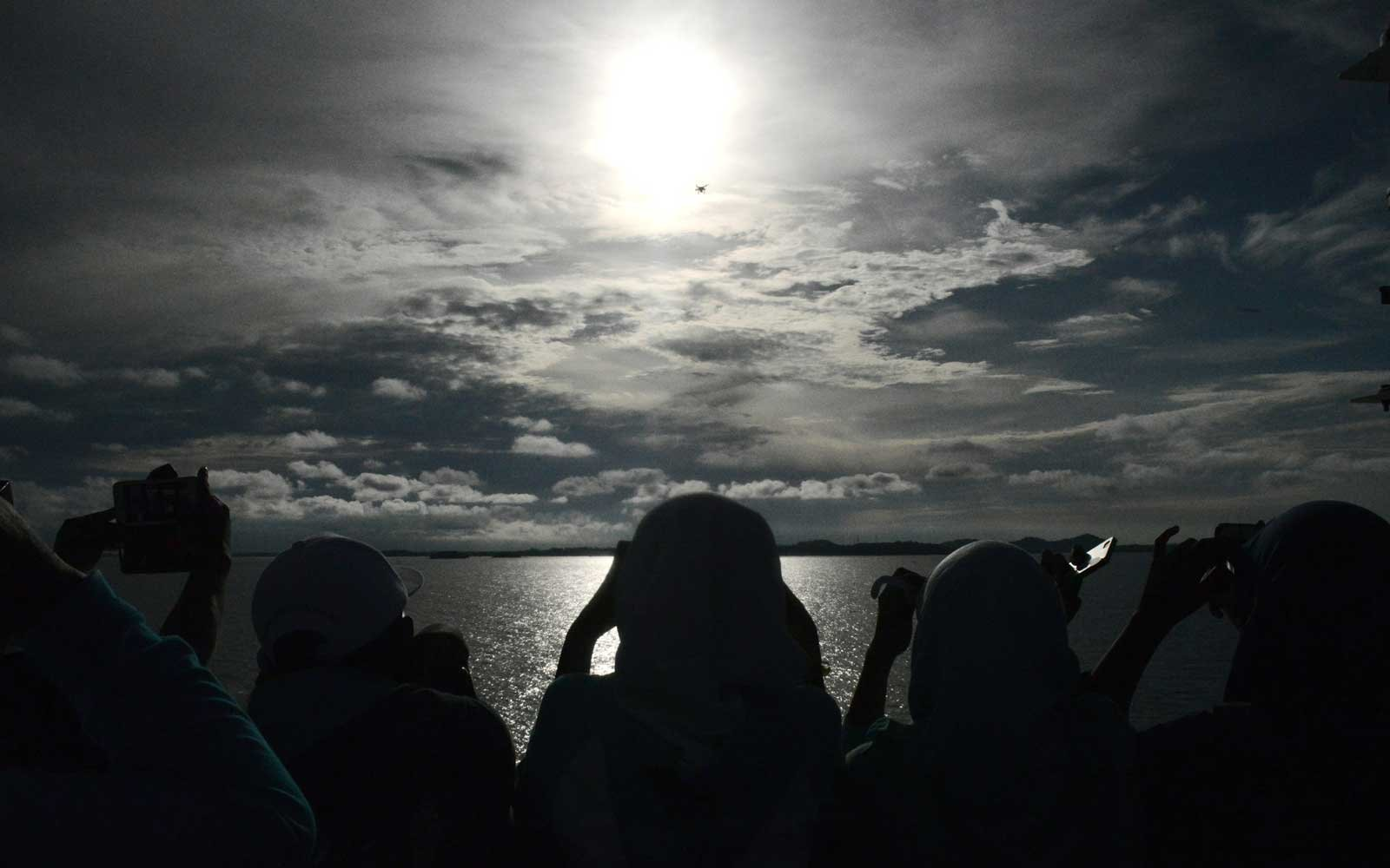 Passengers gather to watch the total solar eclipse onboard the Indonesian cruise ship KM Kelud near the island of Belitung in Indonesia