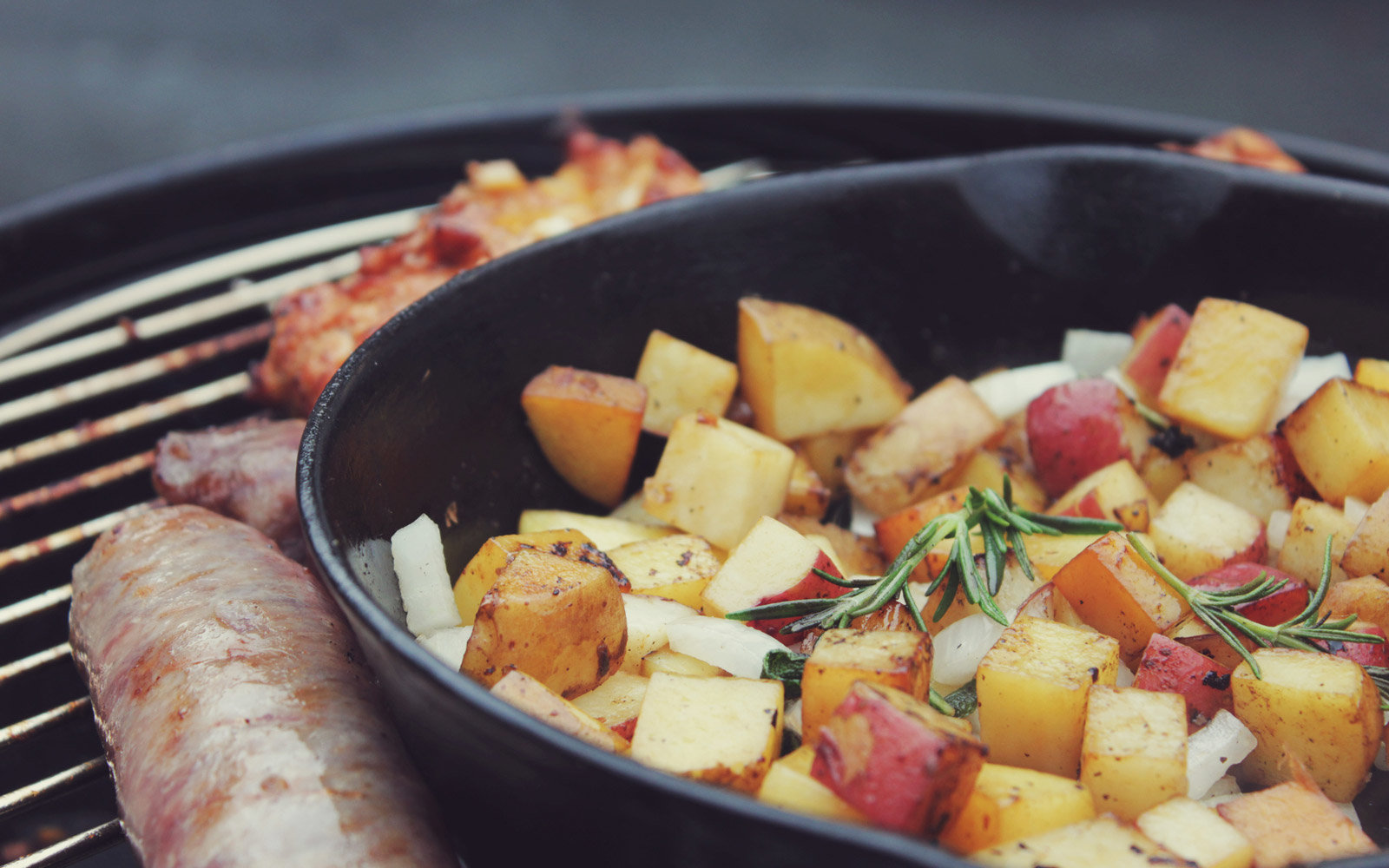 Cast iron skillet sits on grill with potatoes and rosemary inside.