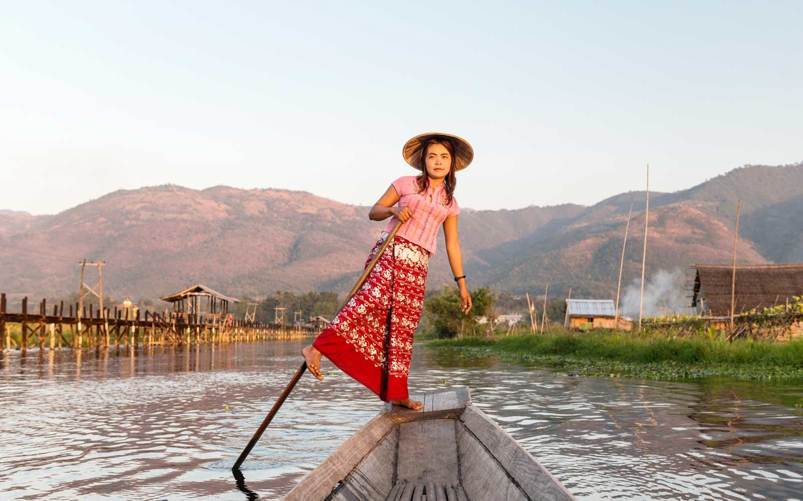 Myanmar, Shan state, Inle lake, woman wearing traditional clothing, rowing boat through water gardens and floating village.