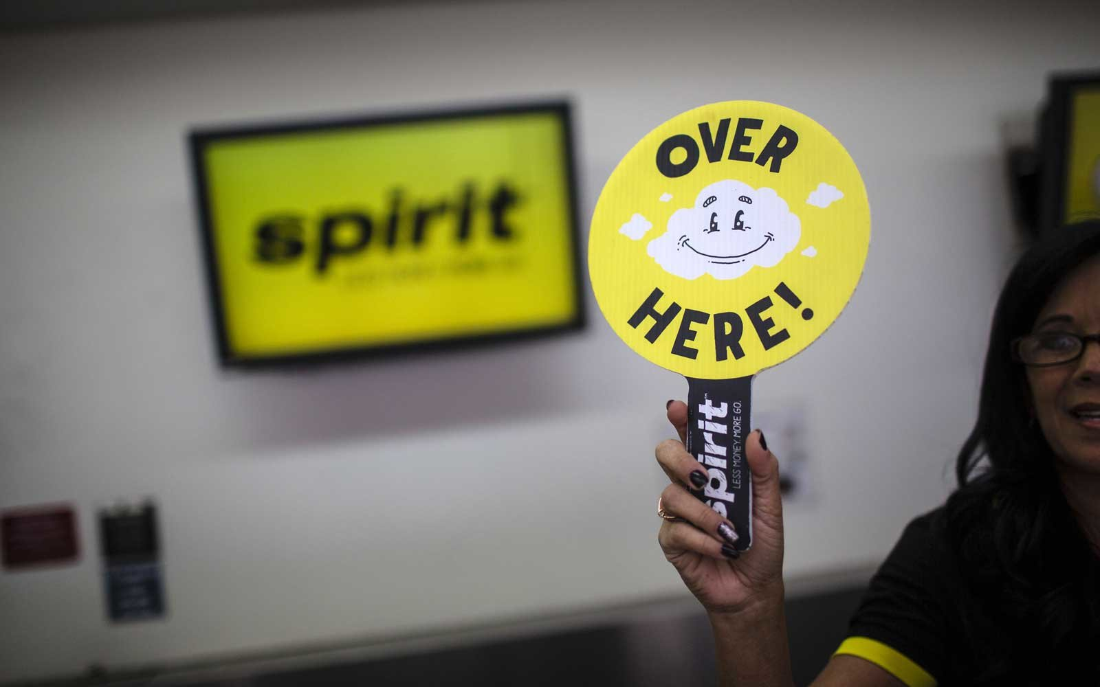 An employee holds a sign to direct travellers at the Spirit Airlines Inc. ticket counter at Fort Lauderdale International Airport (FLL)