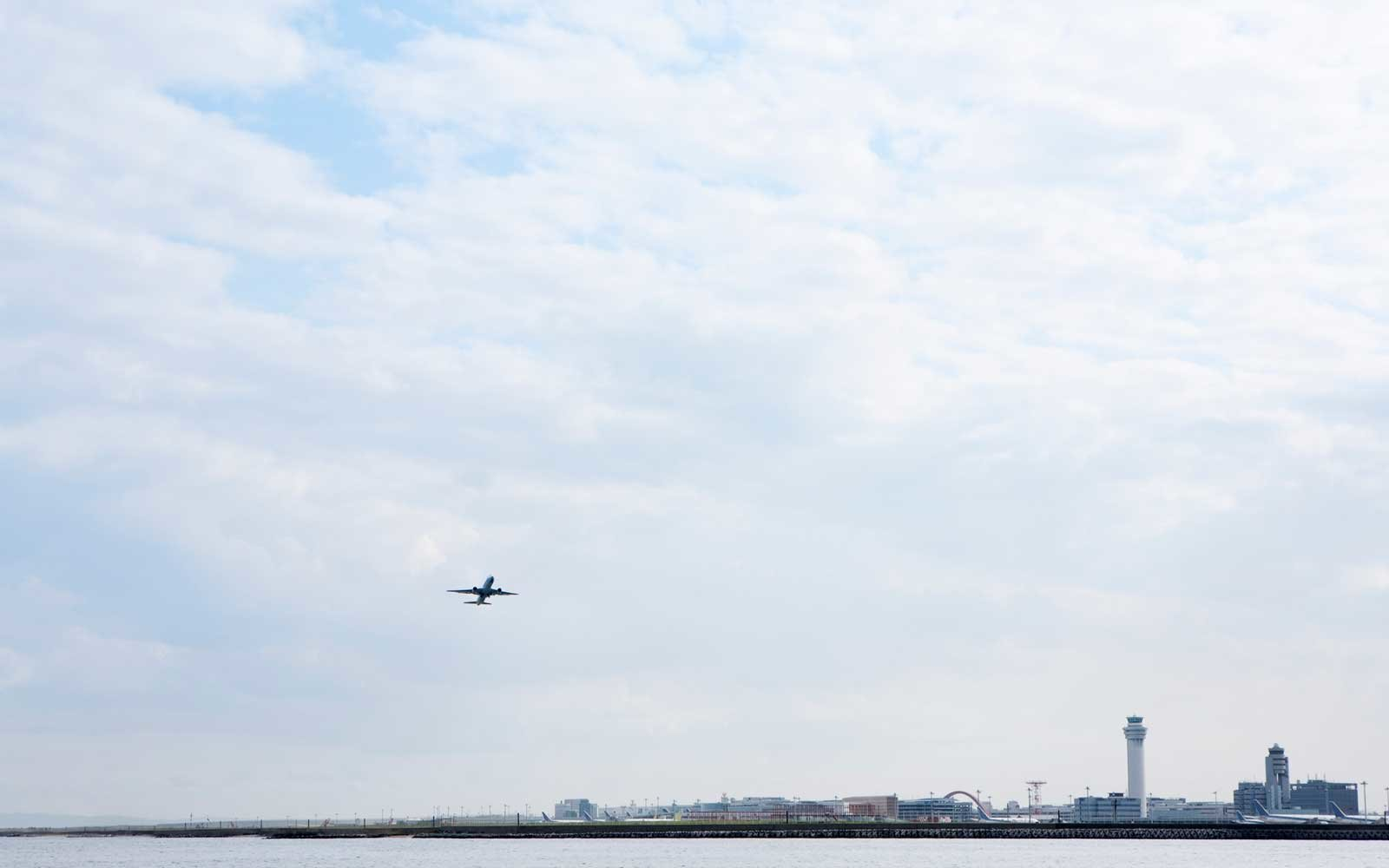 An air plane taking off from  airport on the seashore.