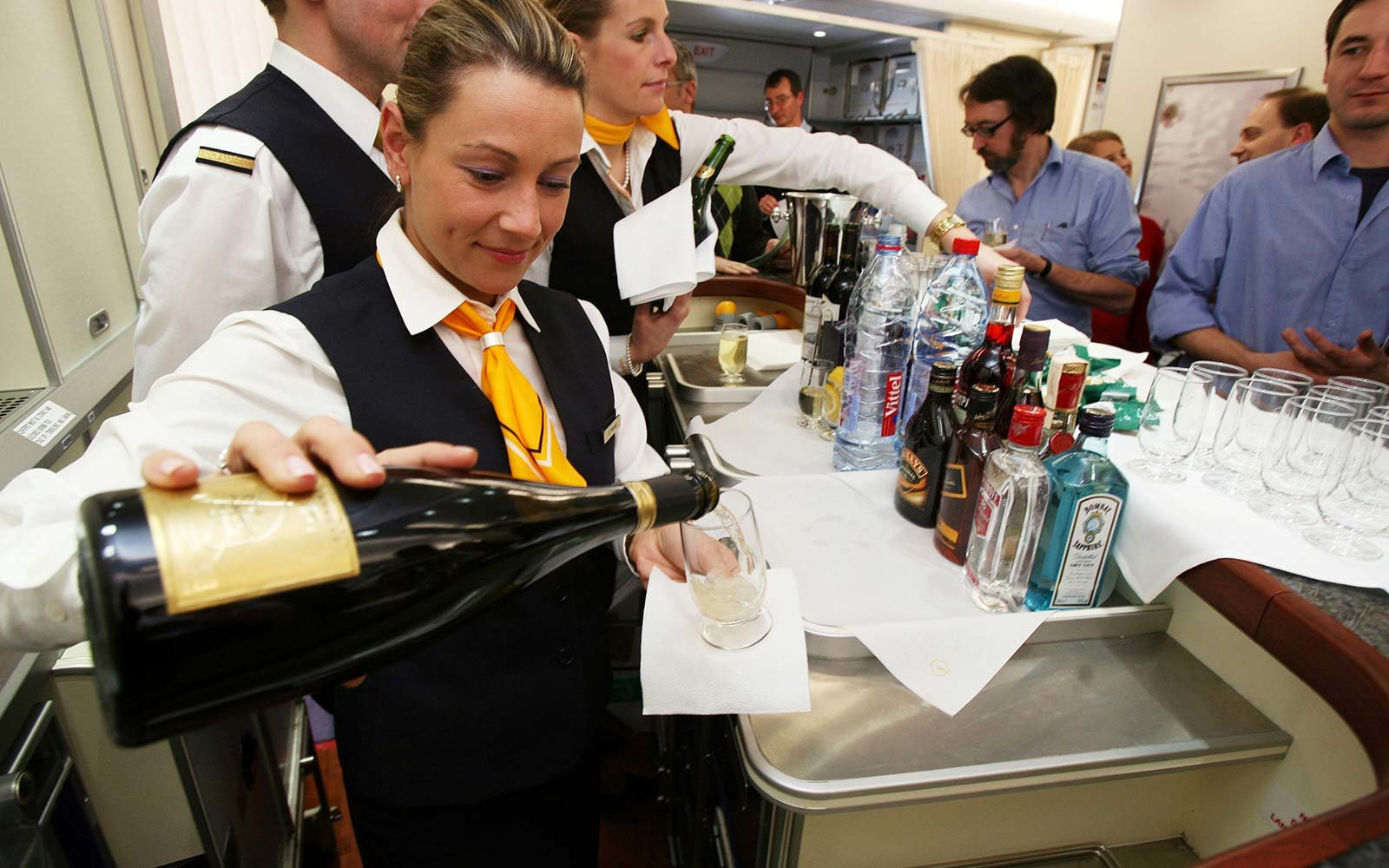 A flight attendant serves champagne on an Airbus A380 airplane at the bar on that model's first transatlantic flight liquor drink bar