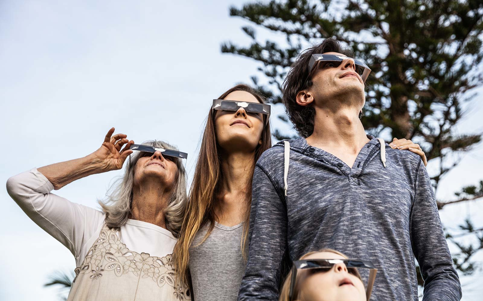 Family looking at Solar Eclipse using solar glasses weather