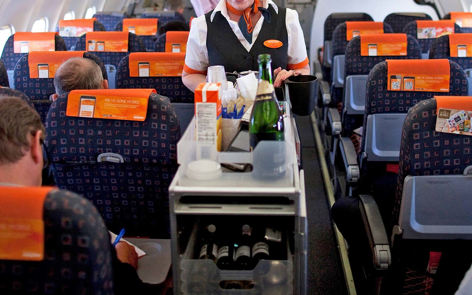 An EasyJet flight attendant serves travelers during a flight from London Southend Airport to El Prat airport in Barcelona, Spain