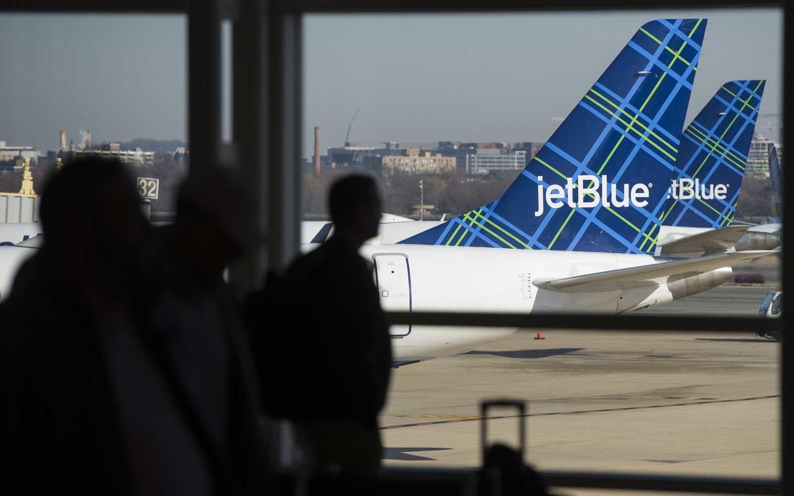Travelers walk past the tails of JetBlue airplanes in the airport terminal