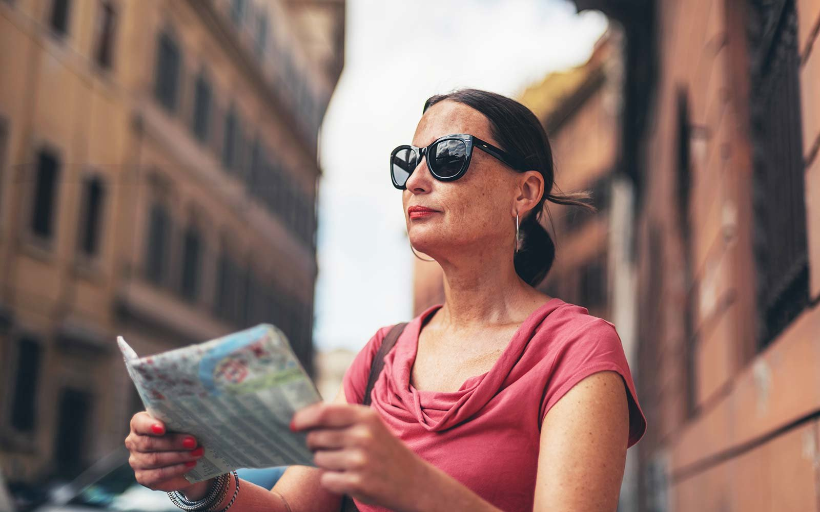 Map reading female tourist with sunglasses in Rome, Italy Solo retirement