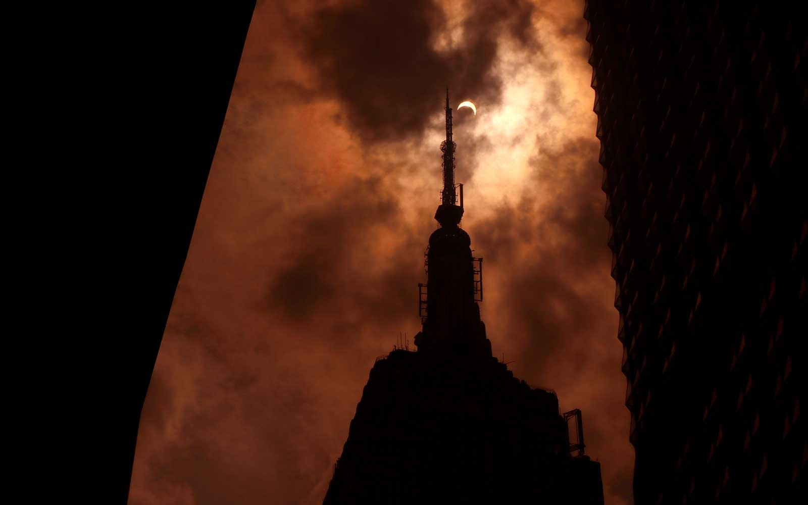 The sun is eclipsed by the moon over top of the Empire State Building in New York City on August 21, 2017.