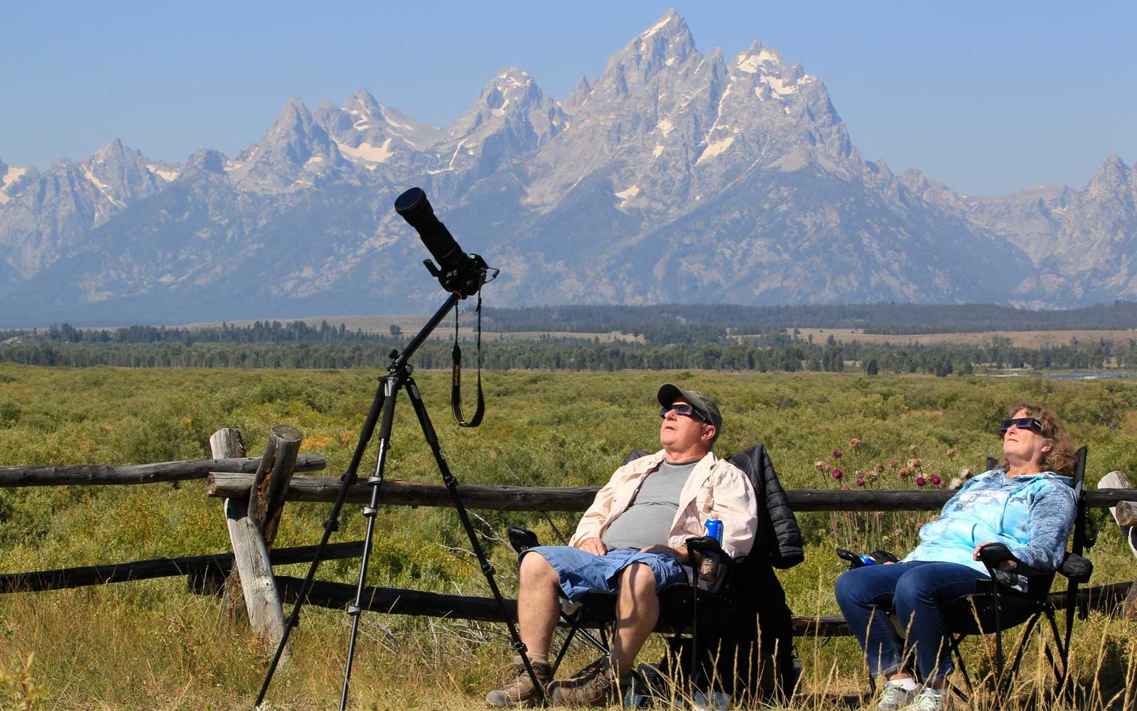 A couple woman views the solar eclipse in the first phase of a total eclipse in Grand Teton National Park on August 21, 2017