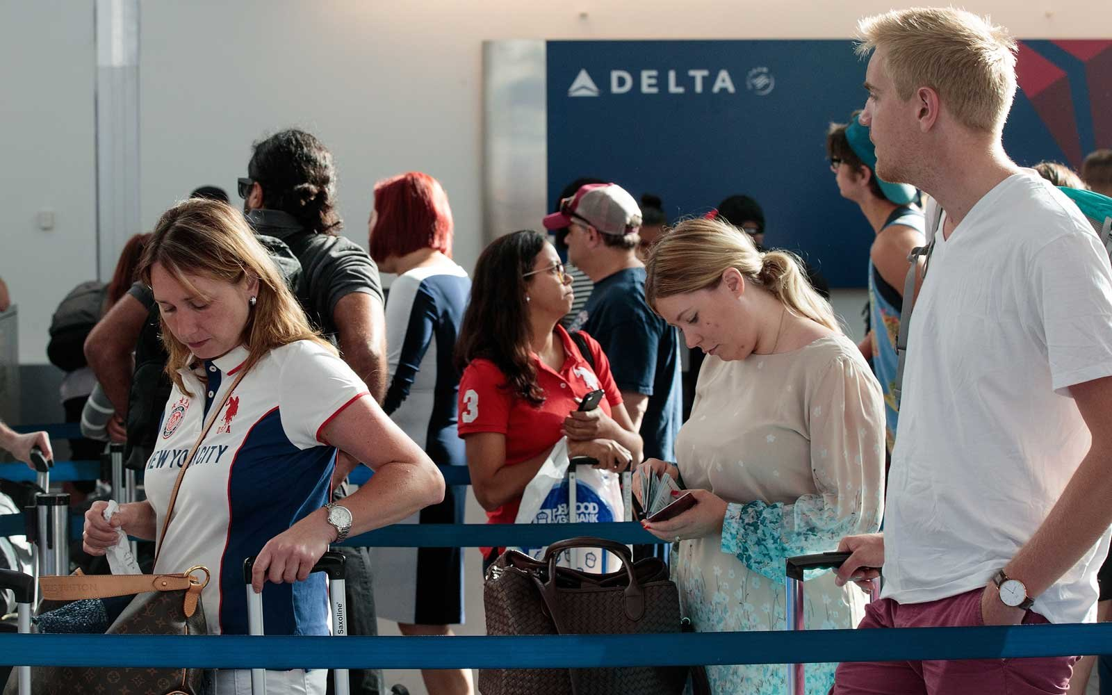 Travelers wait in line at the Delta check-in counter at LaGuardia Airport