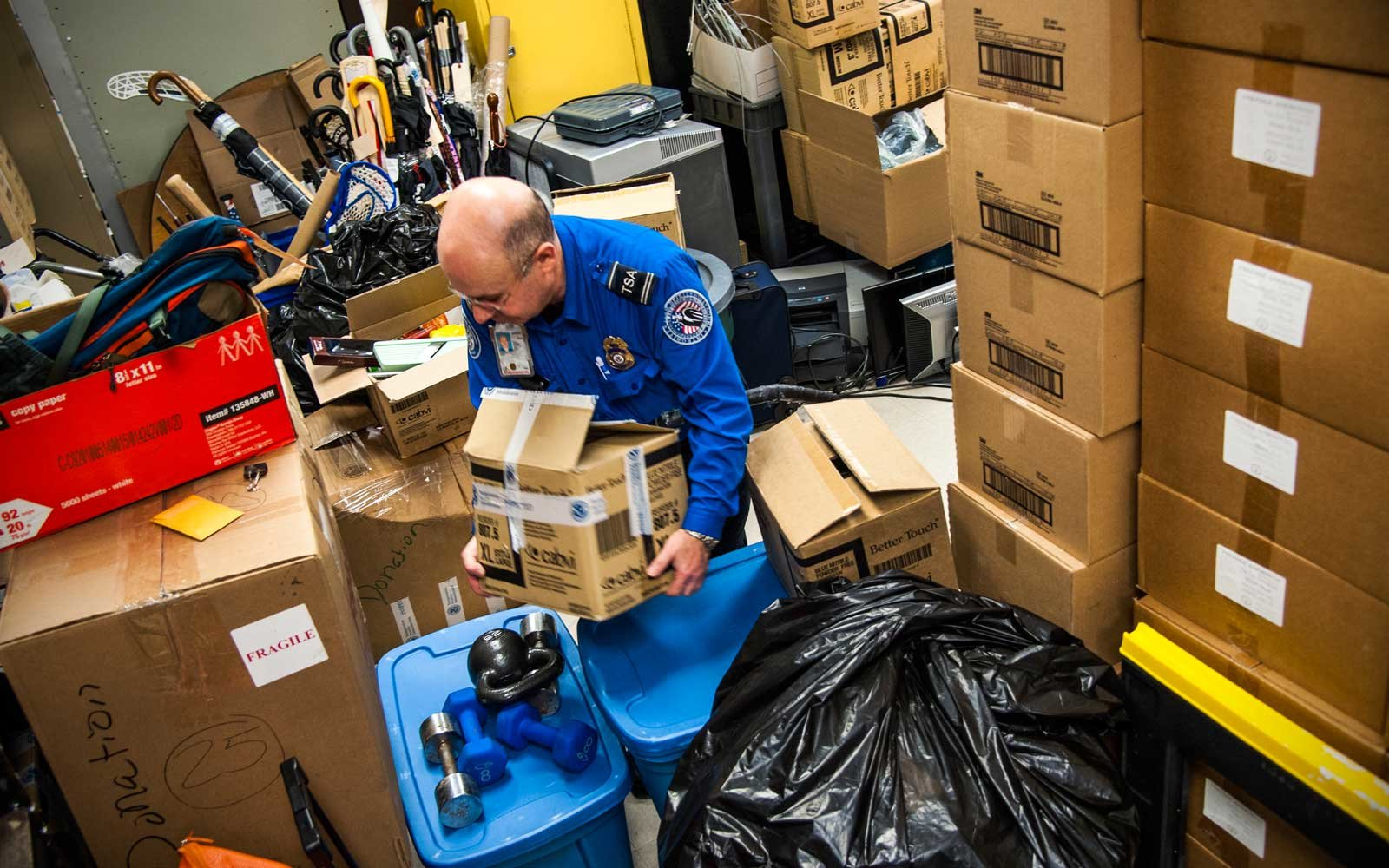 TSA officer Igor Markasyan starts to empty the storage facility at Newark Liberty International Airport