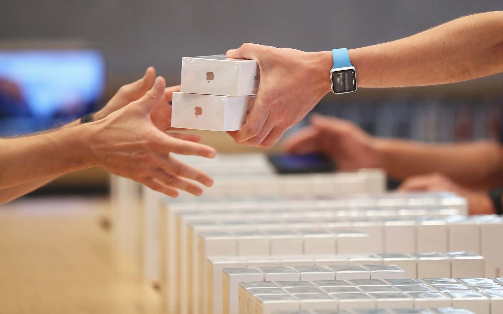 An Apple employee hands over Apple iPhone 7 phones on the first day of sales of the new phone at the Berlin Apple store