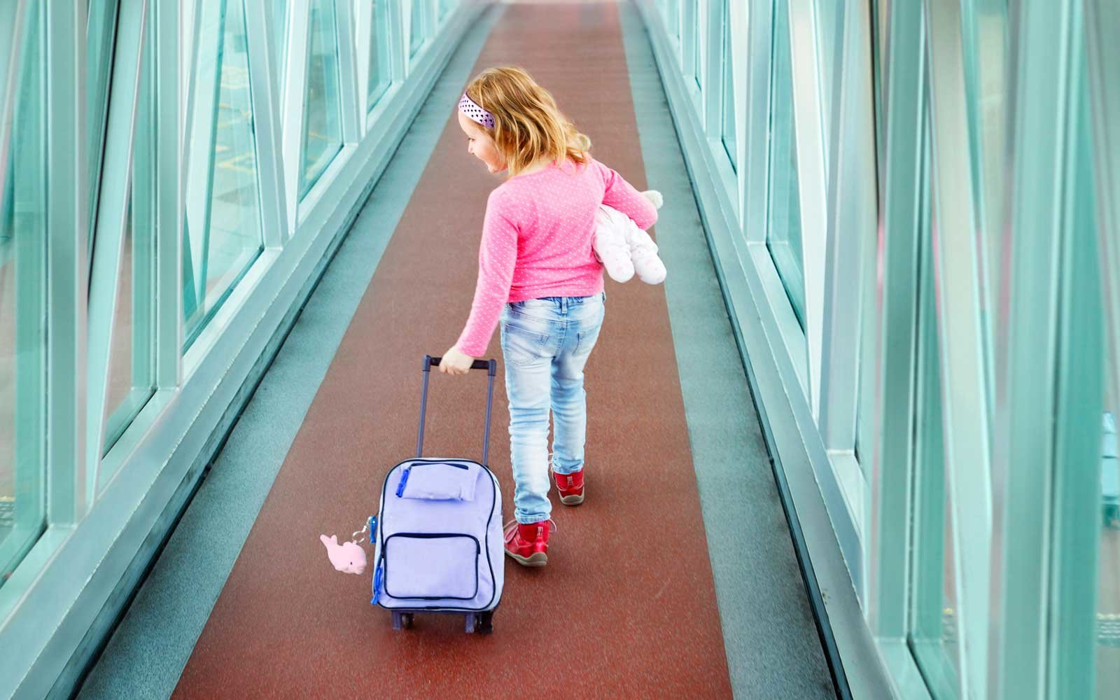 Child Walking With Suitcase in an Airport