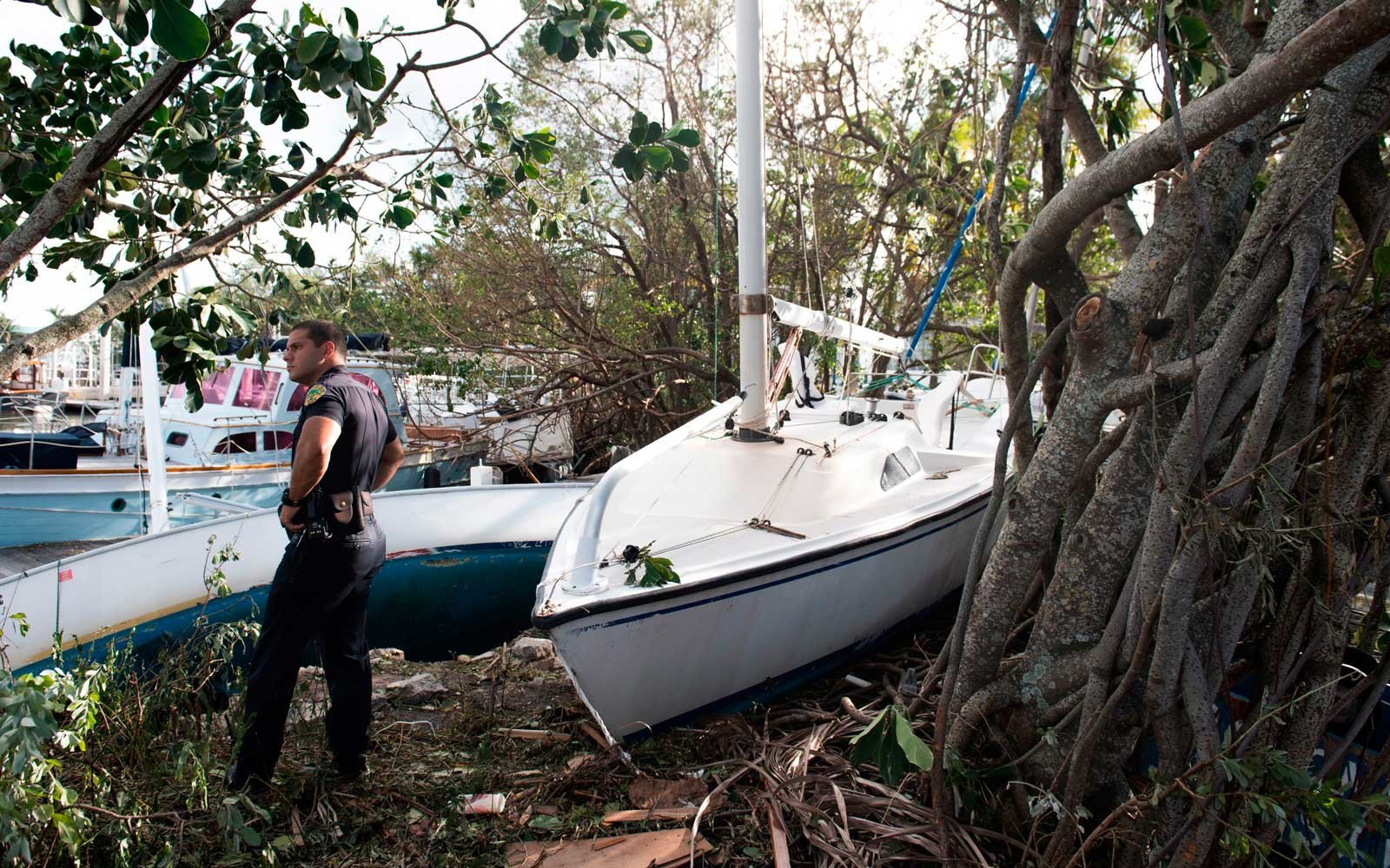 A Miami Police Department Officer looks out over damage and boats brought onto land by Hurricane Irma at a marina in Miami, Florida, September 11, 2017