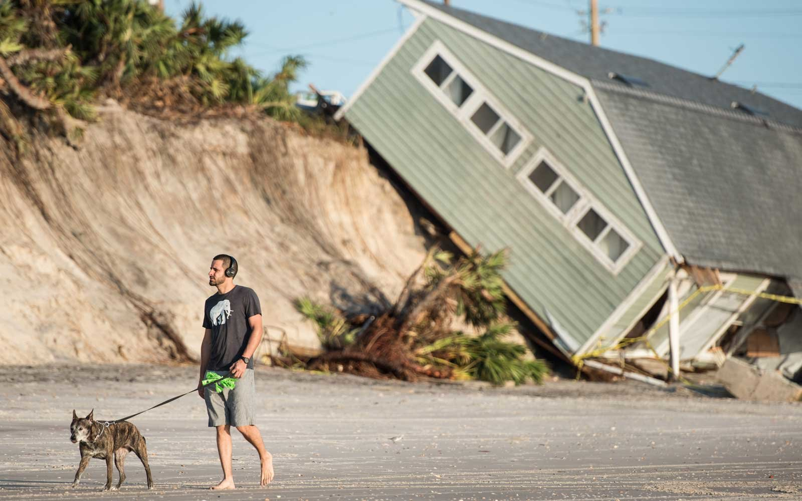 Jose Orosz walks his dog Karen by a beachfront home destroyed by Hurricane Irma on September 13, 2017