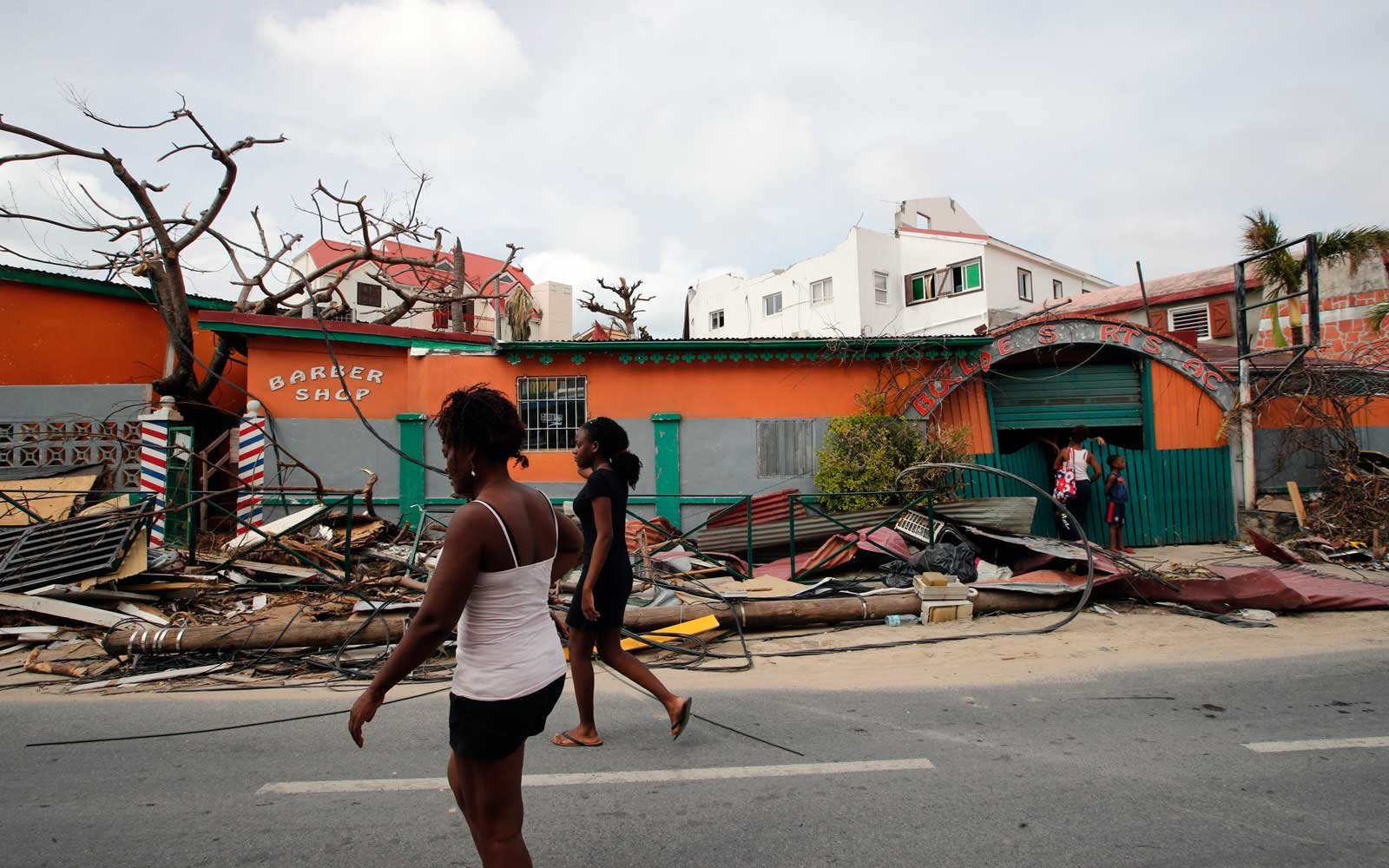 Residents walk in front of homes destroyed by Hurricane Irma on the French Caribbean islands of St. Martin on September 12, 2017